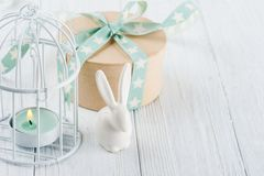 Mint green lit candle in white lantern with gift Royalty Free Stock Photo