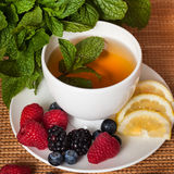 Mint herbal tea. Golden herbal tea with berries and mint leaves in white cup stock images
