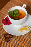 Mint herbal tea. Golden herbal tea with berries and mint leaves in white cup Stock Photo