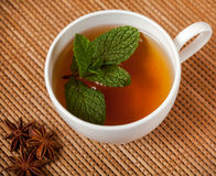 Mint herbal tea. Golden herbal tea with mint leaves in white cup Royalty Free Stock Image