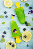Mint ice ice cream with lemon juice and edible flowers of garden viola on a turquoise summer background. Top View. Mint ice ice cream with lemon juice and royalty free stock photos
