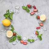 Mint, ice, strawberries and lemon. Refreshing summer lemonade ingredients. As a wreath on grey concrete background with copy space for text Royalty Free Stock Photos