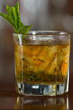 Mint julep cocktail. Refreshing mint julep served on the rocks with a busy bar background Royalty Free Stock Photos