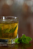 Mint julep cocktail. Refreshing mint julep served on the rocks with a busy bar background Stock Photo