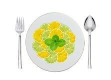 Mint, lemon and lime slices on plate, spoon and fork isolated Stock Photo