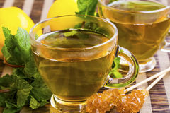 Mint and lemon tea in transparent glass with mint herb and sugar Stock Images