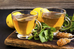 Mint and lemon tea in transparent glass with mint herb and sugar Stock Photos