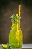 Mint lemonade in the jug with yellow straw and lemons on the table outdoor. Stock Photo