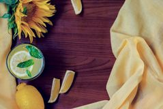 Mint lemonade with lemon slices on a wooden background with a beautiful sunflower, still life photography stock photography
