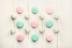 Mint and strawberry flavor macaroons and cake pops on sticks on white background. Collection of mint and strawberry flavor macaroons and cake pops on sticks on Royalty Free Stock Image