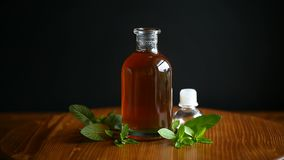 Mint syrup in a glass bottle. On a black background stock video