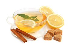 Mint tea. Cup of green tea with mint leaves, lemon, heart-shaped cane sugar and cinnamon sticks on white background stock images