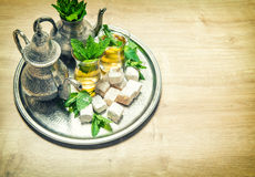Mint tea with arabic delight. Oriental hospitality. Vintage styl Stock Photos
