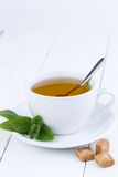 Mint tea with brown sugar on wooden table. Stock Photography