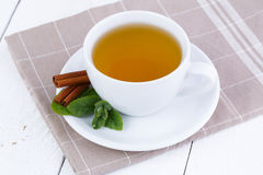 Mint tea with cinnamon on wooden table. Royalty Free Stock Images