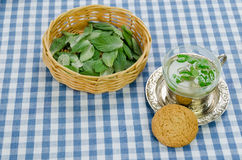 Mint tea in cup and cookie on checkered tablecloth Stock Images