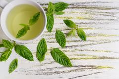 Mint Tea. A cup of mint tea with mint leaves sprinkled around it Royalty Free Stock Image