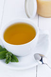 Mint tea with honey on wooden table. Royalty Free Stock Image
