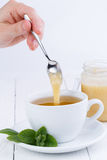 Mint tea with honey on wooden table. Stock Photos