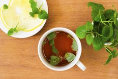 Mint tea with Melissa and lemon. On a wooden table Royalty Free Stock Images
