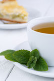 Mint tea with slice of rhubarb pie on wooden table. Stock Photo