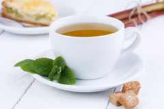 Mint tea with slice of rhubarb pie on wooden table. Royalty Free Stock Image