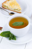 Mint tea with slice of rhubarb pie on wooden table. Royalty Free Stock Photography