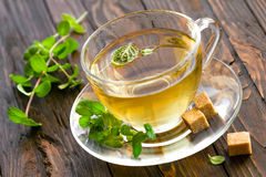 Mint tea. In a transparent glass cup and fresh leaves on a wooden table Royalty Free Stock Photography