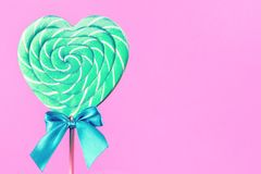 Mint and white spiral heart lollipop isolated on pink backgroun. Mint and white spiral heart lollipop with blue bow isolated on bright pink background. Minimal royalty free stock images