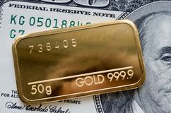 Minted gold bar weighing 50 grams against the background of dollar bill.  stock image