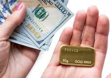 Minted guldtacka som väger 50 gram och några hundra dollarräkningar i hand Arkivbilder
