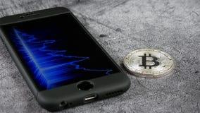 Mintiendo en el bitcoin y el smartphone de la moneda de la tabla, que exhibe el horario de citas de la moneda crypto Comercio ade almacen de video