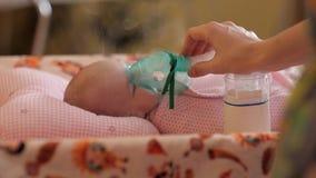 Mintiendo en la cama, dan el niño una inhalación con el dispositivo apropiado Tratamiento de un recién nacido almacen de metraje de vídeo