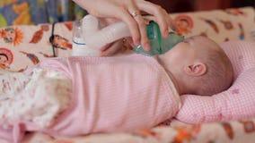Mintiendo en la cama, dan el niño una inhalación con el dispositivo apropiado Tratamiento de un recién nacido metrajes