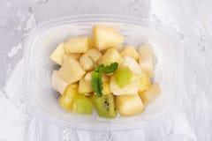 Mintkaramellblad med äpple- och ananasskivor i plast- matbehållare royaltyfria bilder