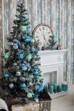 Mintkaramellen färgar julgranen nära den klassiska spisen Arkivfoto