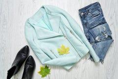 Mintkaramellomslag, svarta skor, jeans och lönnlöv trendigt begrepp Arkivfoto