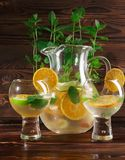 Mintkaramellsidor, gräsplan kalkar och snittapelsiner för en söt sund coctail Frukt- coctail i ett kafé på en tabellbakgrund Royaltyfria Bilder