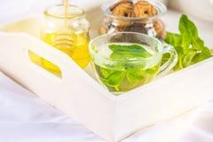 Mintkaramellte i en kopp, en krus av honung, en kaka i en krus, på ett vitt magasin i säng Royaltyfria Foton