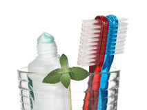 Minty breath. Toothbrushes, toothpaste and mint leaves in a glass over white background Stock Photography