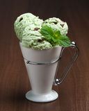 Minty Ice Cream. Mint chocolate chip ice cream in white cup on dark background Stock Image