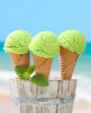 Minty Ice Creams. Three mint ice creams in wafer cones with beach blur background Stock Photo