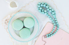 Minty macaroon and teal beads on light background. Mint macaroon and teal beads on light background Royalty Free Stock Image