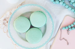 Minty macaroon and teal beads on light background. Pastel mint macaroon and teal beads on light background Stock Photo