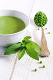 Minty Pea Soup. Mint leaves, peas in a large vintage spoon on a light background Royalty Free Stock Image