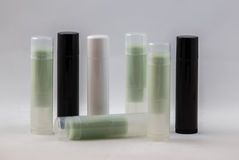Minty Tubes. Arrangement of many white, black, and clear chapstick shaped tubes with green content on a white background Royalty Free Stock Photography