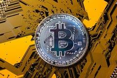 Minujący Bitcoin pojęcie - srebna moneta na koloru żółtego PCB fotografia stock