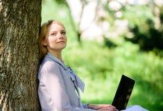 Minute für entspannen sich Mädchenarbeit mit Laptop im Park auf Gras sitzen Ausbildungstechnologie und Internet-Konzept frech lizenzfreie stockfotos