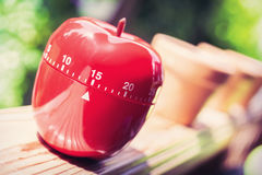 15 Minute Kitchen Egg Timer in Apple Shape Standing On A Handrail Stock Photo