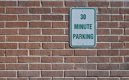 30 Minute Parking. Sign on a brick wall Royalty Free Stock Photography